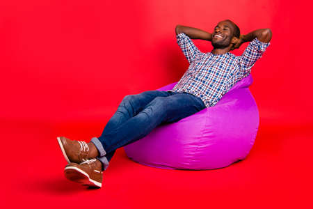 Nice handsome cheerful positive guy wearing checkered shirt sitting on violet purple bag chill out isolated over bright vivid shine red background