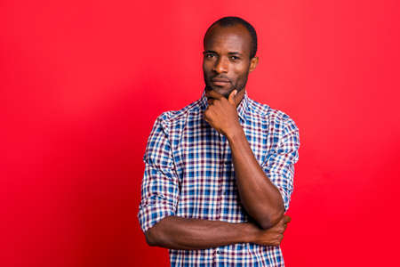 Portrait of nice handsome attractive calm candid guy wearing checked shirt touching chin isolated over bright vivid shine red background Reklamní fotografie