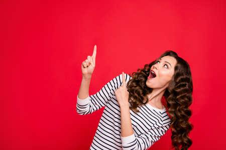Nahaufnahme des Porträts einer schönen süßen Attraktiven, die ihr Mädchen schockiert hat, oh ja, cooles Verkaufen mit dem Finger oben auf dem leeren Raum mit weißem Pullover-Outfit einzeln auf rotem, lebendigem, hellem Hintergrund