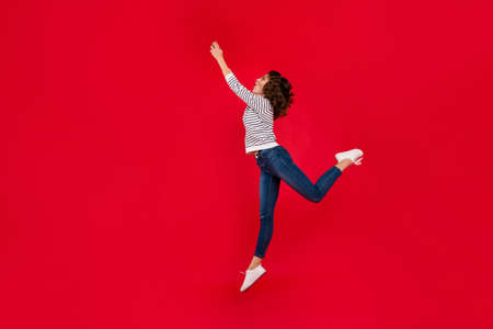 Full length size body photo of fly high in delight with invisible umbrella holding it by hands glad attractive she her girl wearing white casual sweater on red vivid bright background Stock Photo