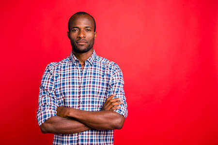 Portrait of nice handsome well-groomed attractive guy wearing checked shirt isolated over bright vivid shine red background