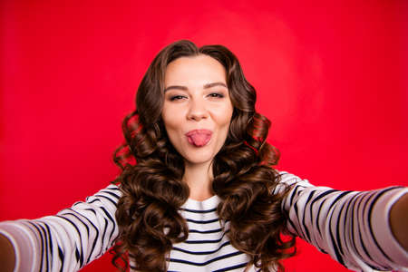 Self-portrait of nice lovely cute gorgeous attractive positive cheerful wavy-haired lady wearing striped pullover showing tongue out isolated over bright vivid shine red background