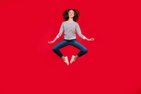 Full length size body photo of fly high pretty charming she her girl getting yoga energy in lotus pose wearing striped white casual sweater on red vivid bright background 免版税图像