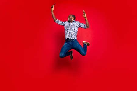 Körpergröße in voller Länge eines netten lustigen, verrückten, attraktiven, fröhlichen, fröhlichen, positiven Kerls, der ein kariertes Hemd trägt, das in den Händen hält, Zellenlesetext einzeln auf hell leuchtendem rotem Hintergrund Standard-Bild