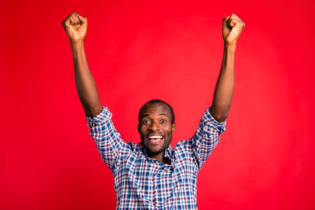 Portrait of nice handsome cheerful cheery glad positive optimistic trendy guy in checked shirt showing breakthrough gesture raising hands fists up isolated over bright vivid shine red background