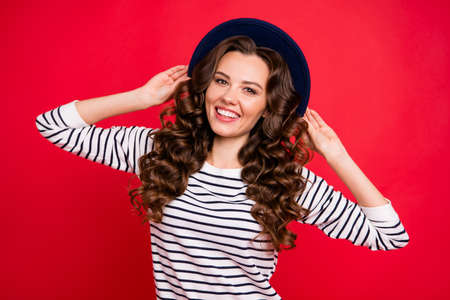 Portrait of nice sweet lovely attractive pretty cheerful positive cheery wavy-haired lady wearing striped pullover touching sunhat isolated over bright vivid shine red background