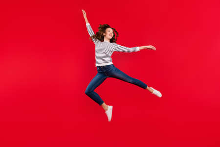 Full length size body photo of fly high attractive beautiful her girl wondering if she makes right movement wearing striped white casual sweater on red vivid bright background Stock Photo