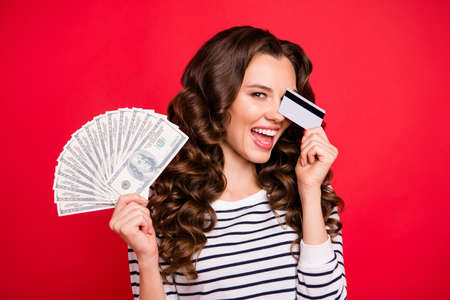 Portrait of nice attractive pretty cheerful wavy-haired lady wearing striped pullover holding plastic card and fan of hundreds usd closing one eye isolated over bright vivid shine red background