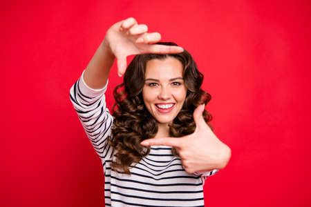 Close up portrait of glad attractive young she her woman with beaming smile making frame with thumbs and forefingers looking through camera isolated on red vivid bright background Stock Photo