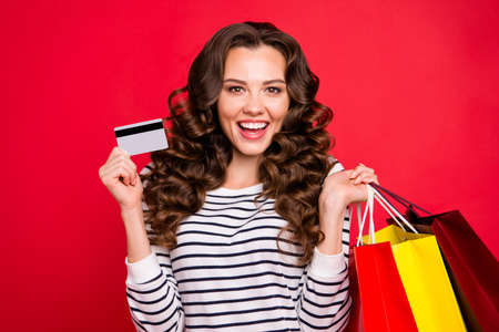 Portrait of nice luxury attractive pretty cheerful wavy-haired lady wearing striped pullover holding in hands bags plastic card isolated over bright vivid shine red background Stock Photo