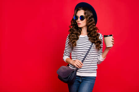 Portrait of nice well-groomed confident content lovely attractive slim wavy-haired lady wearing striped pullover sunhat holding papercup espresso isolated over bright vivid shine red background Stock Photo