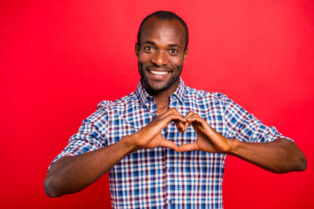 Portrait of he nice handsome attractive cheerful positive optimistic guy boyfriend wearing checkered shirt showing heart shape isolated over bright vivid shine red background Stock Photo