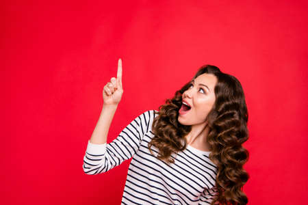 Close up portrait of beautiful cute attractive she her girl with finger in top of empty space shocked with new prices wearing white sweater outfit isolated on red vivid bright background Stock Photo