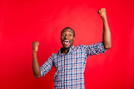 Portrait of handsome cheerful glad optimistic positive guy wearing checked shirt showing fortunate winning gesture holding fists raising hands up isolated over bright vivid shine red background