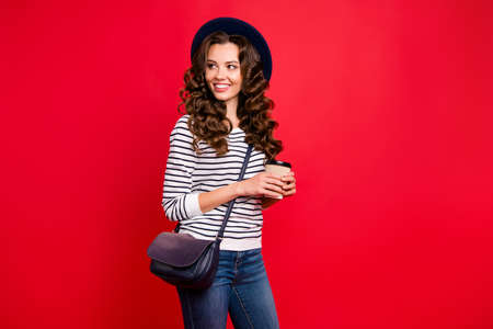 Portrait of nice lovely attractive cheerful slim wavy-haired lady wearing striped pullover sunhat holding papercup isolated over bright vivid shine red background Stock Photo