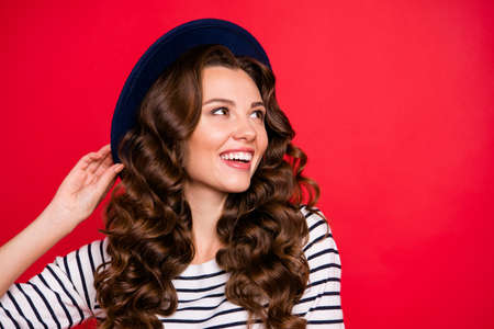 Close-up portrait of nice sweet lovely winsome attractive cheerful cute wavy-haired lady wearing striped pullover sunhat dreaming about vacation isolated over bright vivid shine red background Stock Photo