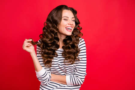 Close up portrait of attractive pretty cheerful she her girl mouth open gladly laughing with funny joke with one curl in hand white striped pullover isolated on red vivid background