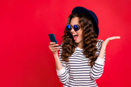 Portrait of nice funny lovely attractive cheerful positive wavy-haired lady in striped pullover eyeglasses eyewear sunhat reading sms opened mouth isolated over bright vivid shine red background