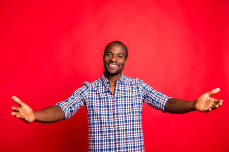 Come to me! Portrait of nice handsome attractive cheerful cheery guy wearing checked shirt wide hands hugs isolated over bright vivid shine red background