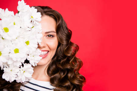 Close-up half-face portrait of nice cute lovely sweet attractive cheerful positive wavy-haired girl hiding holding smelling white flowers isolated over bright vivid shine red background