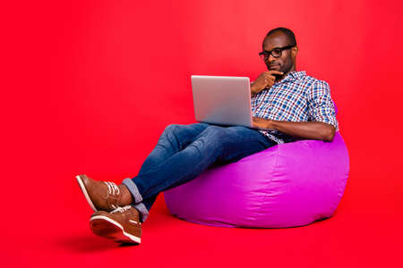 Nice calm focused concentrated handsome guy wearing checked shirt working remotely on laptop creating presentation sitting on violet bag isolated over bright vivid shine red background