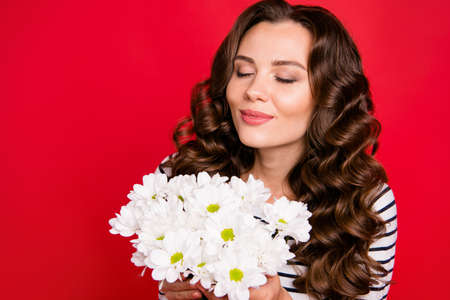 Close-up portrait of cute lovely sweet tender gentle adorable pretty attractive wavy-haired girl wearing striped pullover smelling flowers closed eyes isolated over bright vivid shine red background