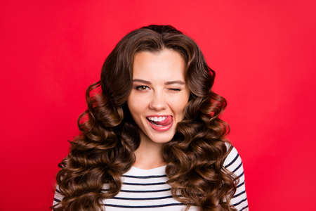 Close up portrait of cheerful attractive she her girl with flirt touching lower lip by tongue amazing wave hair settled on shoulders white striped pullover isolated on red bright vivid background