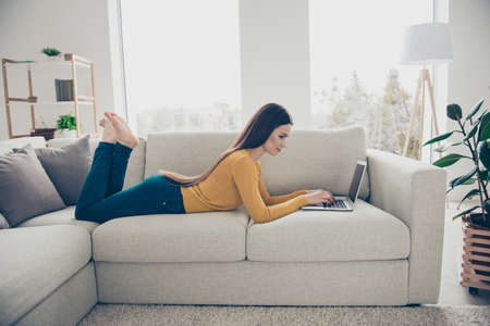 Profile side view portrait of nice lovely attractive charming calm peaceful focused clever smart straight-haired girl lying barefoot on divan preparing homework task email in light interior room
