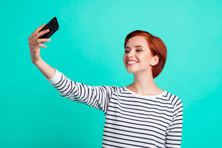 Close up portrait of beautiful cheerful ginger attractive she her lady with telephone in hand taking self photos toothy smiling wearing white striped pullover isolated on teal background