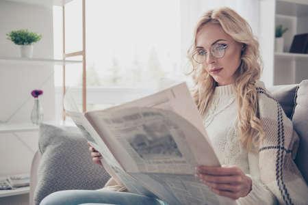 Portret van een leuke, aantrekkelijke, intelligente huisvrouw met golvend haar die een trui draagt die in handen een interessante samenvatting leest in een lichte binnenkamer Stockfoto
