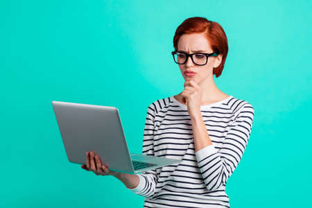 Clever pondering pensive deciding doubtful serious touching chin with short hairstyle bright business lady solving problem using network cowork holding notebook in hand isolated bright teal background Stock Photo