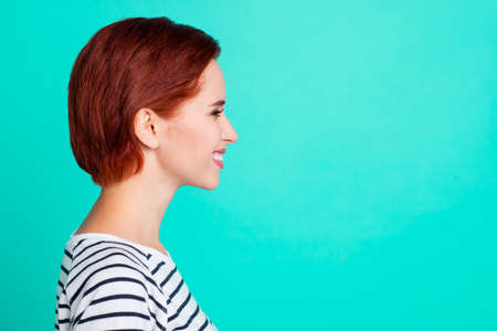 Profile side view portrait of her she nice charming pretty sweet attractive cheerful cheery red-haired lady wearing striped pullover isolated over bright vivid shine green turquoise background 免版税图像