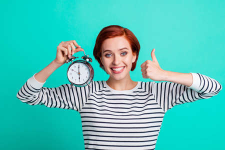 Closeup photo portrait of pretty cute dreamy charming gorgeous nice glad ecstatic crazy she her millennial showing arrows on clockface isolated on bright turquoise background