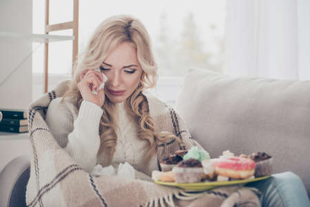 Portrait of broken heart dumped by boyfriend girlfriend gloomy worried wavy-haired lady on divan crying big large plate of tempting seductive homemade baked sweets in light interior room 스톡 콘텐츠 - 113835156