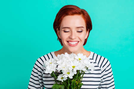 Close up portrait of cheerful attractive foxy she her lady with closed eyes smelling camomile in hands glad mothers day wearing white striped sweater isolated on teal background