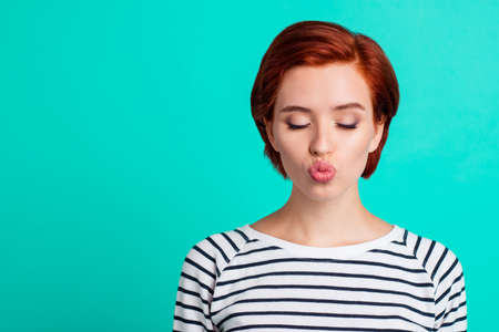 Close-up portrait of her she nice lovely sweet attractive adorable red-haired lady in striped pullover sending air kiss closed eyes isolated over bright vivid shine green turquoise background