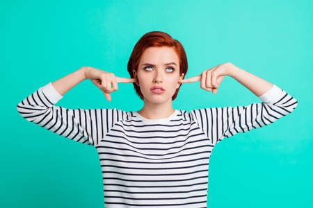 Portrait of nice pretty charming attractive sad red-haired lady wearing striped pullover rolling eyes up closing ears with forefingers isolated over bright vivid shine green turquoise background Stock Photo - 113837041