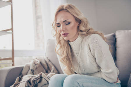 Portrait of nice attractive glamorous stylish gloomy wavy-haired lady wife housewife in sweater sitting on divan writhing in pain early term pregnancy in light white interior room