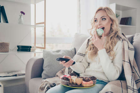 Portrait of nice lovely funny attractive winsome fascinating wavy-haired lady sitting on divan with large big plate of tempting seductive homemade sweets switching channels in light interior room Stock Photo