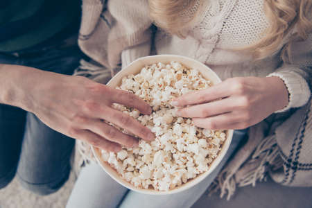 Cropped close-up top above high angle view of two hands taking popcorn big large corn box calories junk food in cozy comfort place