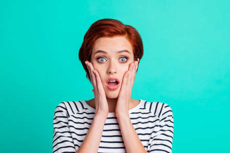 Close-up portrait of nice charming attractive lovely pretty shocked red-haired lady in striped pullover palms on cheeks isolated over bright vivid shine green turquoise background