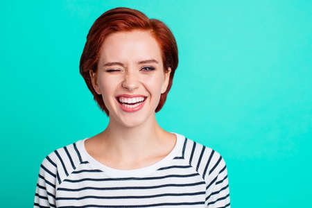 Close-up portrait of nice cool winsome charming attractive cheerful positive flirty red lady wearing striped pullover blinking isolated over bright vivid shine green turquoise background Stock fotó