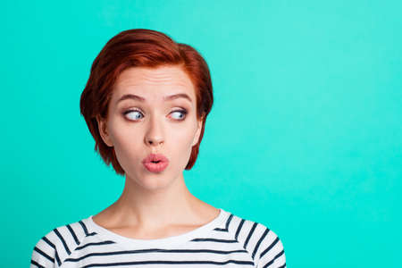Close-up portrait of nice funny charming attractive lovely sweet red-haired lady in striped pullover air blow pouted lips looking aside isolated over bright vivid shine green turquoise background