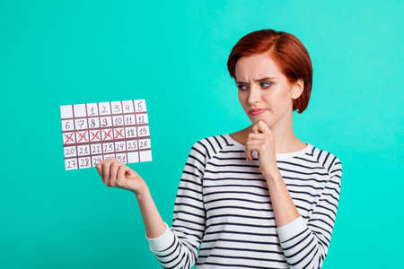 Close up portrait of attractive she her lady holding calendar in hands confused frustrated these days not coming wearing white striped sweater isolated on teal background