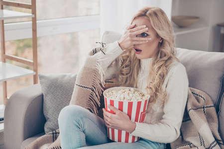Porträt einer schönen, attraktiven, stylischen, lustigen, erstaunten, gewellten Hausfrau, die einen Pullover trägt, der auf einem Diwan sitzt und in den Händen eine Maisbox hält, die ein Video anschaut, öffnete den Mund im hellen Innenraum Standard-Bild