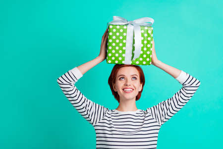 Close up portrait of attractive beautiful she her lady holding large gift box on head desire to unbox it and learn what is there looking up wearing white striped sweater isolated on teal background Stock Photo