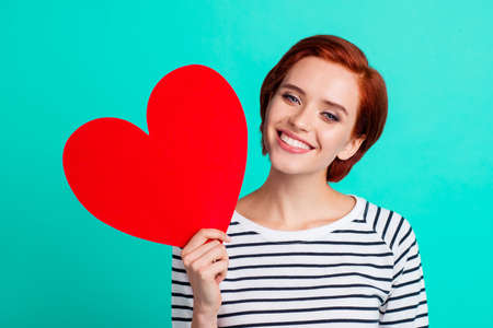 Close up portrait of attractive foxy beautiful she her lady holding large red paper heart in one hand suit to fire red short hairstyle hairdo in white striped sweater isolated on teal background