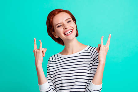 Portrait of her she lovely cool trendy stylish attractive cheerful red-haired lady wearing striped pullover showing two double horns isolated over bright vivid shine turquoise background