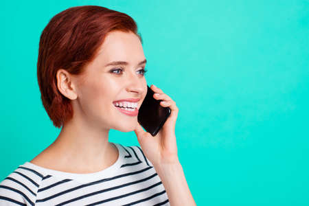 Close up portrait of beautiful cheerful foxy attractive she her lady with telephone in hand glad to hear old friend from Canada USA wearing white striped pullover isolated on teal background