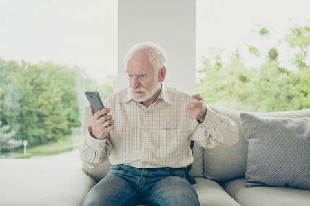 Portrait of mad gloomy old man sitting on divan holding in hand Stock Photo